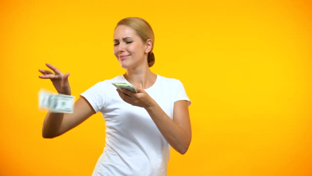 sorglös kvinna kastar dollar runt, rika kvinnliga slösar pengar, konsumism - spendera pengar bildbanksvideor och videomaterial från bakom kulisserna