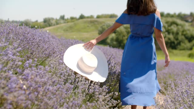 Carefree woman with hat runs through floral glade