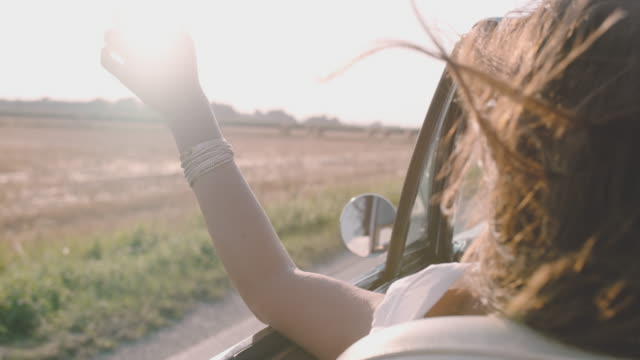 slo mo carefree young woman driving convertible along sunny, rural field - дуть стоковые видео и кадры b-roll