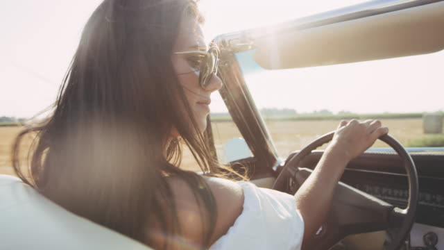 cu carefree young woman driving convertible along sunny, rural fields - soft focus video stock e b–roll