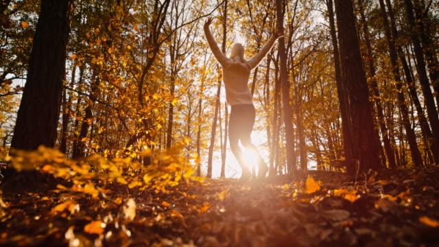 ms super slow motion giovane donna spensierata che salta per la gioia nei boschi autunnali soleggiati e idilliaci - autunno video stock e b–roll