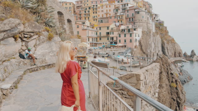 MS Carefree young woman walking along railing, Cinque Terre, Italy