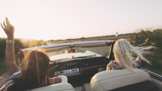 MS Carefree young women driving convertible on sunny, rural road video