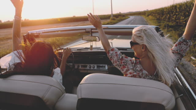 MS SLO MO Carefree young women with arms raised driving convertible along sunny, rural road