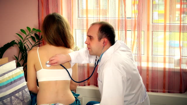careful man doctor in white smock examining young female woman patient video