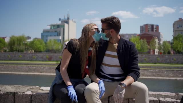 保護フェイスマスクを着用しながらキスしようとする慎重なミレニアル世代のカップル ビデオ
