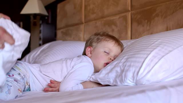försiktig mamma döljer filt på ett sovande barn. - cosy pillows mother child bildbanksvideor och videomaterial från bakom kulisserna