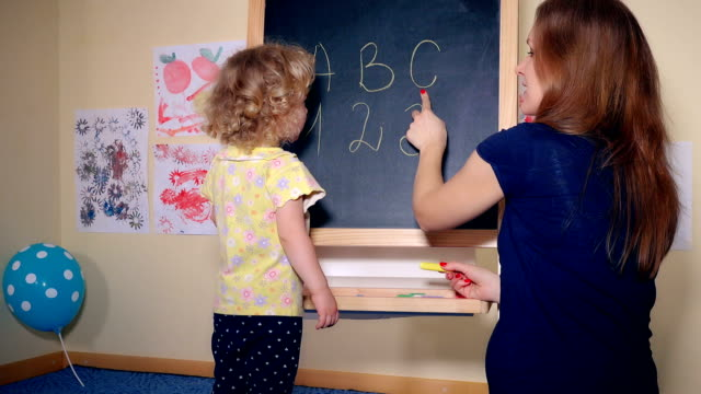 Careful teacher woman teaching smart child girl letters and numbers