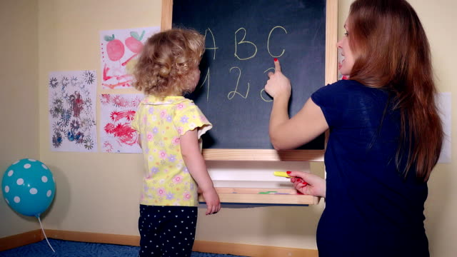 Careful teacher woman teaching smart child girl letters and numbers video