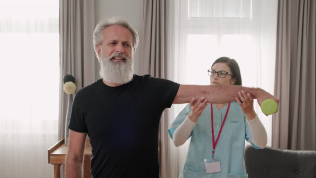 caregiver helping mature man with exercise - fisioterapia video stock e b–roll