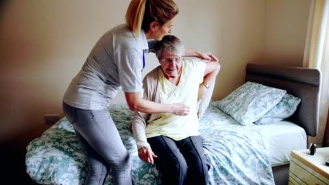 vídeos de stock e filmes b-roll de caregiver helping senior woman dress - cuidado