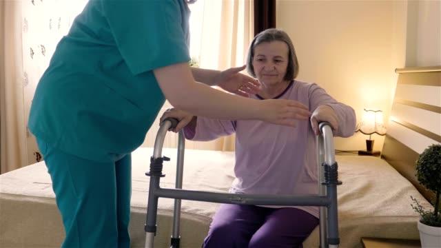 Mujer senior de cuidador ayuda a levantarse y caminar con un andador - vídeo