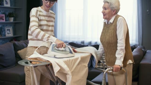 caregiver ironing for senior woman - nonna e nipote camminare video stock e b–roll