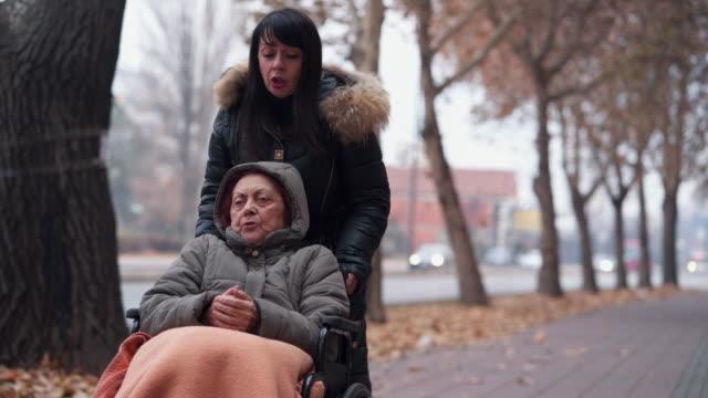 caregiver spinge paziente anziana su sedia a rotelle - fragilità video stock e b–roll