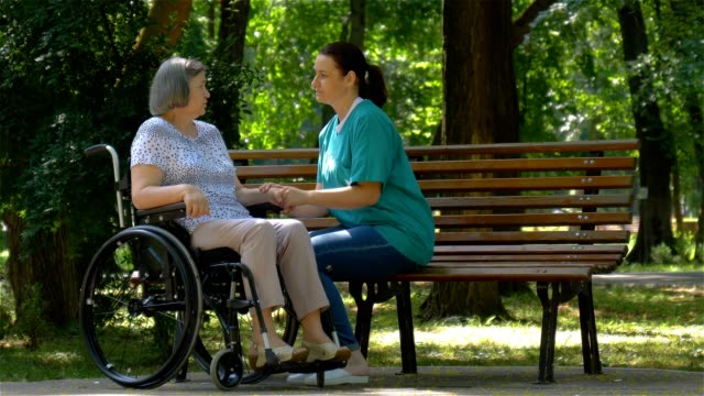 Caregiver talking to disabled senior woman in wheelchair outdoors video