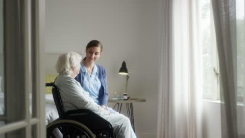 caregiver parla con donna seduta su sedia a rotelle - accudire video stock e b–roll
