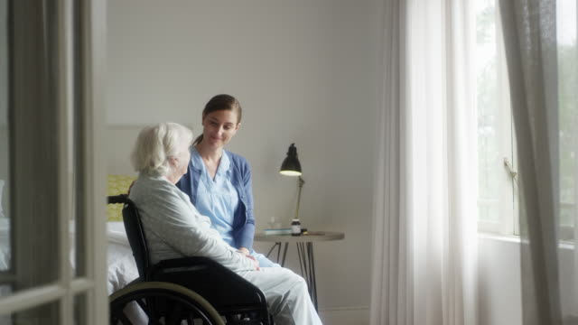 Caregiver talking with woman sitting on wheelchair Slow motion of nurse talking with elderly woman sitting on wheelchair. Senior female patient is with caretaker in bedroom. They are looking through window. aging process stock videos & royalty-free footage