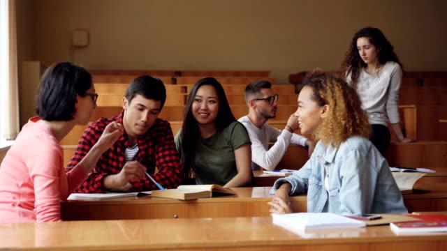Chicos y chicas descuidadas están hablando y riendo sentado en pupitres en el aula, los estudiantes son relajantes durante las vacaciones. Conversación, educación moderna y el concepto de juventud. - vídeo
