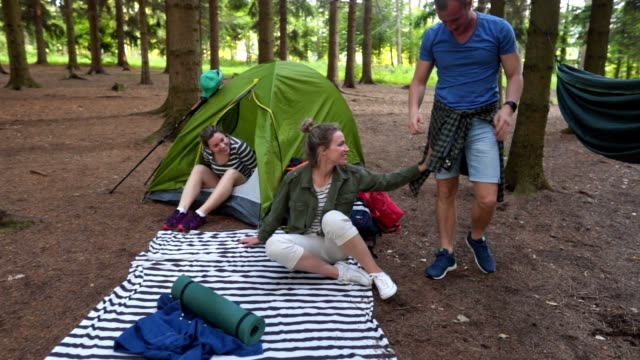 Careless man falling out of the hammock while camping with friends Group of hikers sitting at a camp in a forest. misfortune stock videos & royalty-free footage