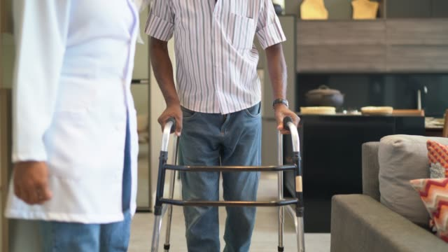 vaktmästare assisterar senior man med walker - fysiotherapy bildbanksvideor och videomaterial från bakom kulisserna