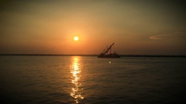 gün batımında kargo teknesi, marina di ravenna, italya - ravenna stok videoları ve detay görüntü çekimi