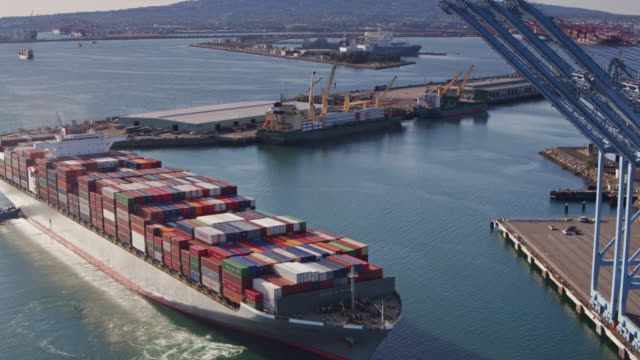 Cargo Ship Arriving Into Dock Beneath Line of Cranes video