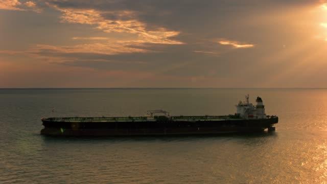 AERIAL Cargo ship at sea as sun is peeking through dark clouds