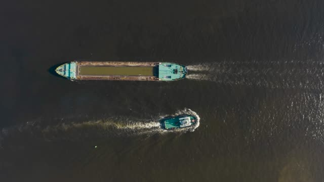 cargo ship barge and tugboat sail to meet each other in the seaport of the port, aerial view - chiatta video stock e b–roll