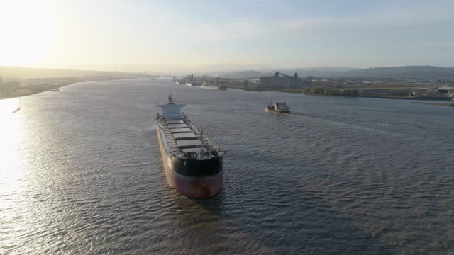 Cargo ship on anchorage at Columbia River, on the border between states Oregon and Washington, USA. A small boat passing in the backdrop. Drone aerial low altitude video with the panning camera motion.