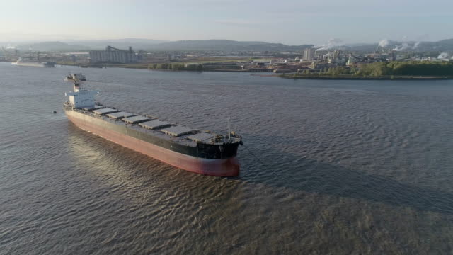 Cargo ship on anchorage at Columbia River, on the border between states Oregon and Washington, USA. A small boat passing in the backdrop. Drone aerial low altitude video with the wide-orbit, panoramic camera motion.