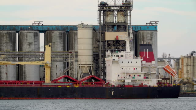 A cargo ship on dock on a factory near the sea video