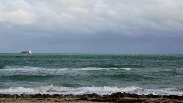 Cargo ship sailing away on a cloudy day video