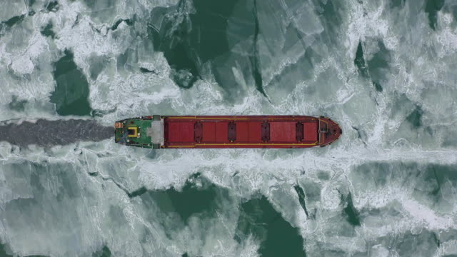 Cargo ship sailing on frozen sea in extreme winter conditions aerial shot. Sailing in narrow fairway channel made by icebreaker vessel. Water transportation during cold winter season in north