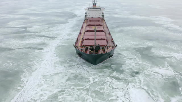Cargo ship sailing on frozen sea in extreme winter conditions aerial shot. Sailing in narrow fairway channel made by icebreaker vessel. Water transportation during cold winter season in north Sailing in narrow fairway channel made by icebreaker vessel. Water transportation during cold winter season in north. industrial ship stock videos & royalty-free footage
