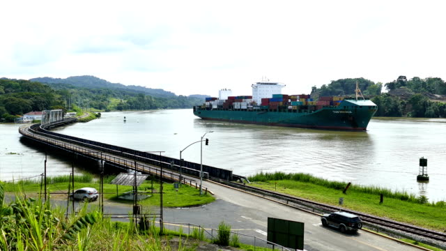 Cargo ship sailling slowly through Panama Canal with small bridge video