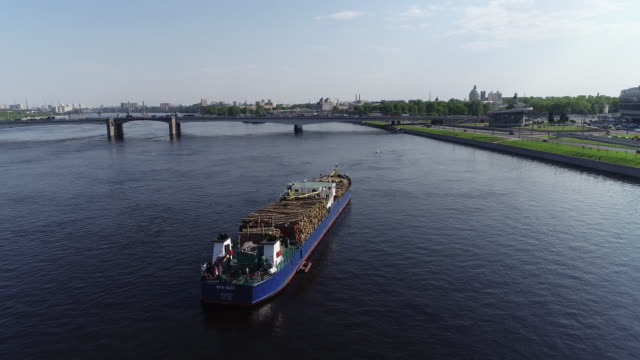 Cargo ship with timber is on river near shore in summer day Cargo ship with timber is on river near shore in summer day, large vessel with wood freight is on water in picturesque city with quay and bridge under blue sky. Concept: wooden industry, modern business, shipping. timber stock videos & royalty-free footage