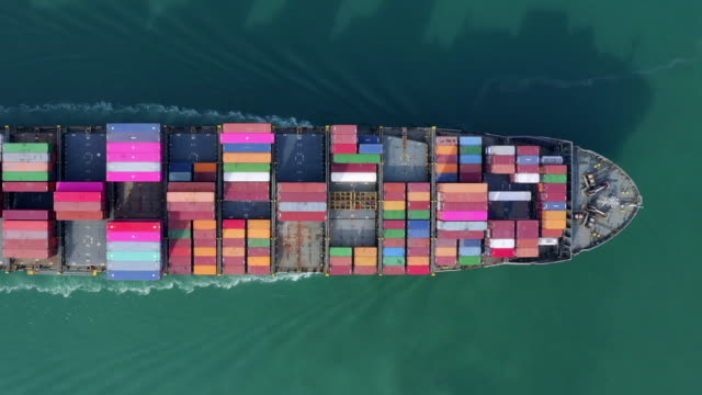 Cargo ships are sailing at sea, transporting goods all around the world.