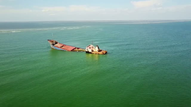 Cargo shipwreck stranded on low level waters near the shore of Sulina City , Danube Delta, Black Sea ,Romania, aerial view video