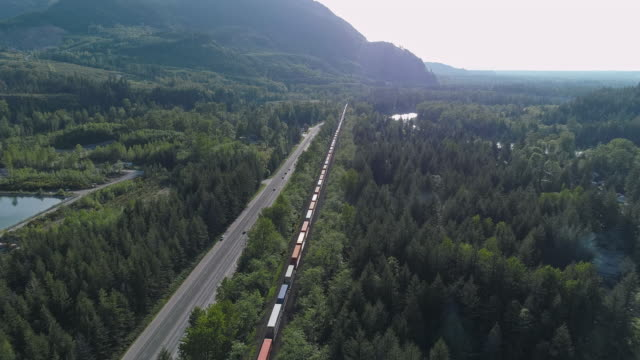 Cargo train carrying containers passing on by railroad in mountains nearby video with the forward camera motion following the train.