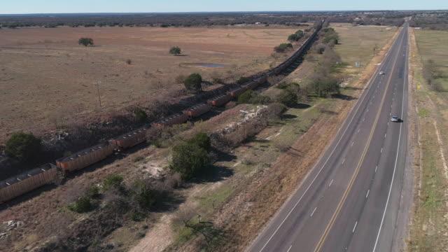 미국 텍사스의 건조한 고원인 에드워즈 고원의 사바나 초원의 고속도로를 따라 철도를 지나가는 화물 열차. 전방 카메라 모션과 공중 무인 항공기 비디오, 기차를 따라. - 전원 장면 스톡 비디오 및 b-롤 화면