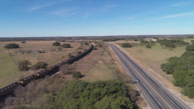 Cargo train passing on a railroad along a highway in savanna grassland on Edwards plateau, the arid highland in Texas, USA. Aerial drone video with the forward camera motion, following the train. Cargo train passing. Texas, USA. 4K UHD aerial video footage. texas stock videos & royalty-free footage