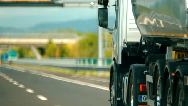 Cargo transport. Closeup side rear view of a semi truck with driving on a highway. Shot from a vehicle passing by wide angle stock videos & royalty-free footage