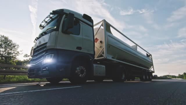 last bil med bränsle diesel last trailer körning på en motorväg. white truck levererar varor i tidiga timmar på morgonen - shipping sunset bildbanksvideor och videomaterial från bakom kulisserna