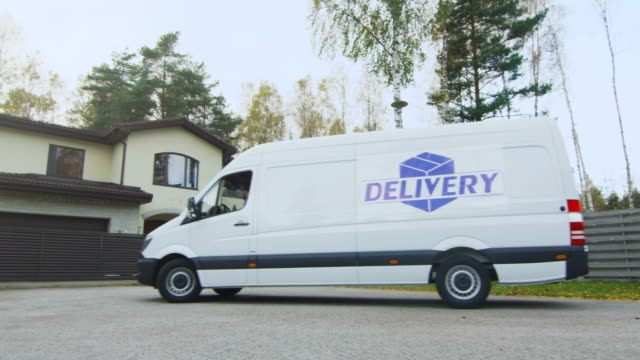 cargo van drives to suburban house and delivery man comes out. sunny autumn with yellow birches and pines is on the background. - furgone video stock e b–roll