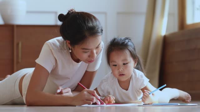 stockvideo's en b-roll-footage met het geven aziatische mum die kinddochter helpt die beeld met potloden trekt - aziatische etniciteit