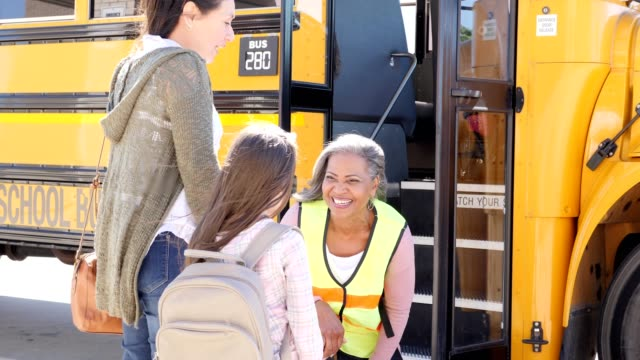 caring bus driver talks to young girl on her first day of school - bus driver stock videos and b-roll footage
