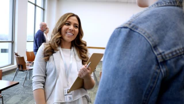 vídeos y material grabado en eventos de stock de consejero atento da la bienvenida a nuevo cliente a sesión de terapia grupal - profesional de salud mental