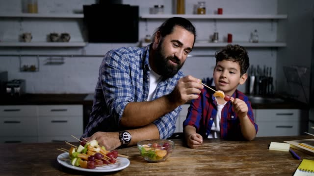 caring dad and son making delicious fruit kebabs - padre single video stock e b–roll