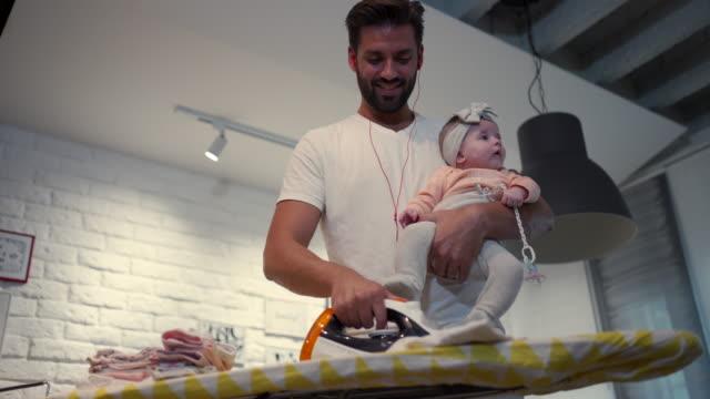 彼の小さな女の子に傾向がある間、家事をしている思いやりのあるお父さん ビデオ