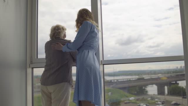 stockvideo's en b-roll-footage met het geven dochter die oude moeder koestert, die zich dichtbij het venster bevindt, dat stad bekijkt - raam bezoek